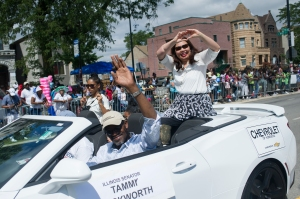 "US Senator Tammy Duckworth signs a ""heart"" to parade watchers during the 88th annual Bud Billiken Parade, Saturday, August 12, 2017."