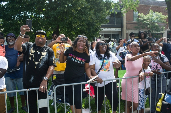 Parade watchers react as parade Grand Marshal Chance the Rapper drives by during the 88th annual Bud Billiken Parade, Saturday, August 12, 2017.