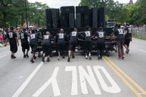 A group of young men push the sound system for the South Shore Drill Team during the 88th annual Bud Billiken Parade, Saturday, August 12, 2017.